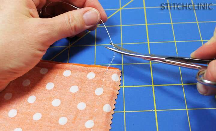 Trimming thread off a sewn piece of fabric