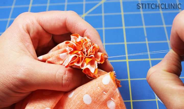 finished sewing bottom of fabric pumpkin, all the fabric bunched together.