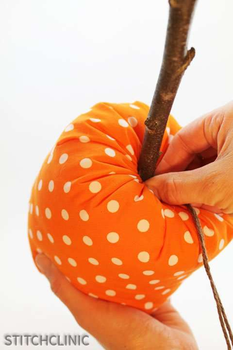 Shoving the yarn down into the middle of the pumpkin