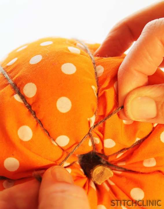 Tying off the yarn on the bottom of the pumpkin