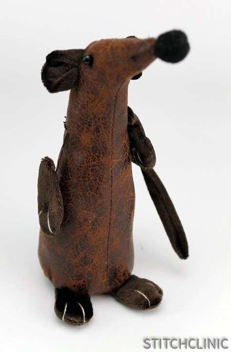 A cute little rat stuffed animal in need of repair