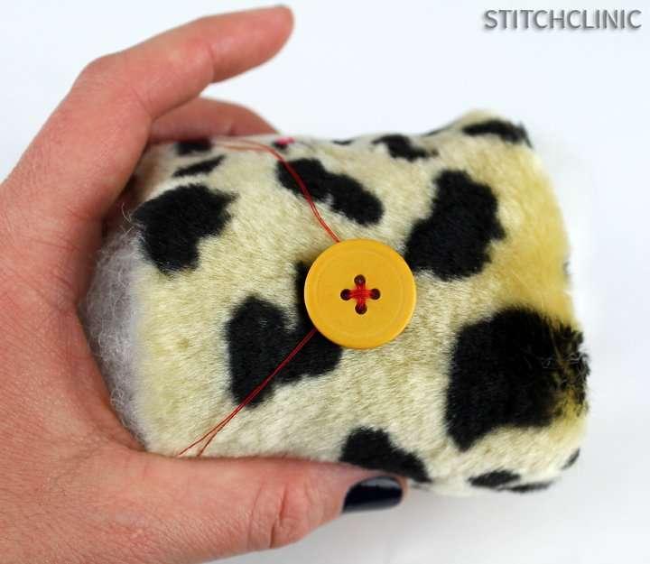button sewn onto stuffed animal