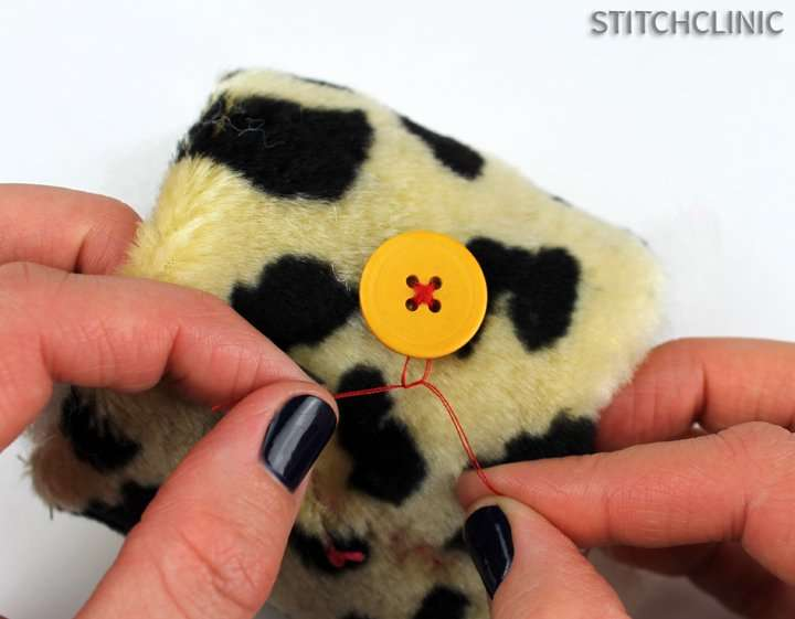 Tying knots to secure button on stuffed animal