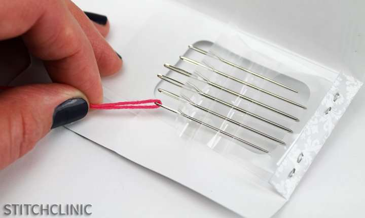 pulling out a needle that is stuck in the package by threading it and pulling on the thread.