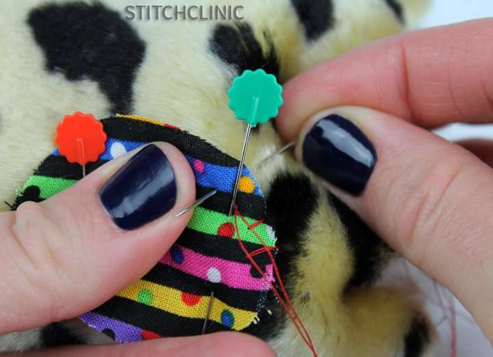 Stitching around the edge of fabric to secure it to fur
